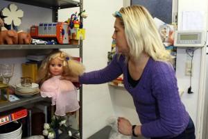 Sabine Walter bringt den Puppenkopf vom Container ins Regal.