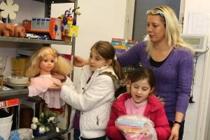 Sabine Walter zeigt Ermedina (links) und Elsa das Spielzeugregal.