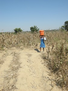 Noch vor der Schule holt die elfjährige Chimwemwe Wasser für die Familie. (Foto: dpa)