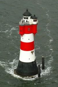 Das ist der Leuchtturm Roter Sand. Er steht vor der Stadt Bremerhaven im Wasser. In diesem Leuchtturm kann man heute übernachten. (Foto: dpa)